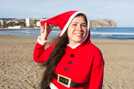 Christmas, holidays and people concept - young happy woman in Santa Claus suit near the sea