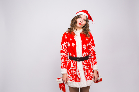 Young woman in red christmas santa claus costume fooling around on white background with copy space Stock Photo