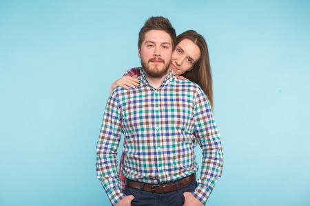 Portrait of cheerful funny young lovers on blue background Standard-Bild