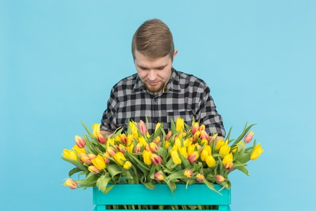 Handsome white male gardener making a bouquet of tulips in blue studio.