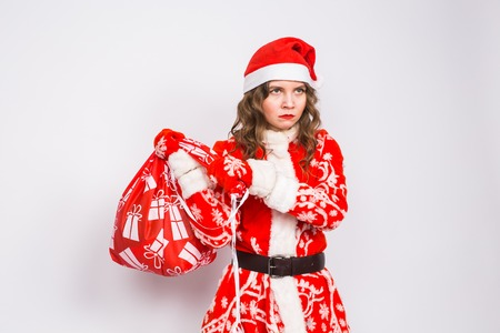 Christmas, emotions and people concept - angry woman in santa claus clothes holding presents on white background