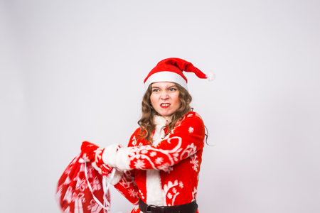 Holiday, Christmas and people concept - Angry woman in santa costume with bag of presents