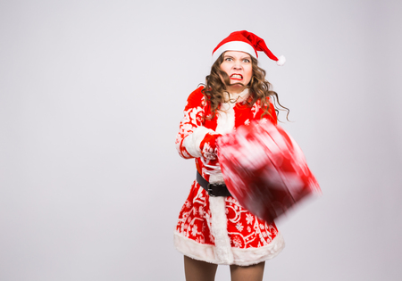 Christmas, emotions and people concept - angry woman in santa claus clothes holding presents on white background with copy space