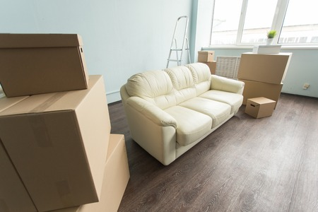 Relocation, moving and real estate concept- a new white sofa in empty room between an amount of boxes