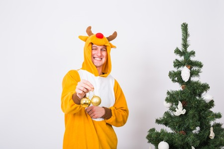 Joke, christmas, people concept - man in deer costume decorating xmas tree on white background Stock Photo