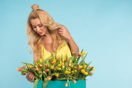 Charming blonde female florist sorts out tulips in the box, selects them for the future flower arrangement Imagens
