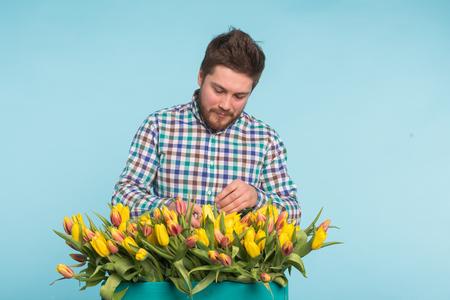 Handsome caucasian male gardener making a bouquet of tulips in blue studio. Stock fotó