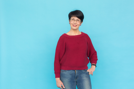 Fashion, style and people concept - middle aged pretty woman over turquoise background with copy space