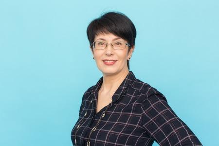 Mode-, Menschen- und Stilkonzept - Schöne Frau mittleren Alters mit Brille, die auf blauem Hintergrund mit Kopierraum lacht