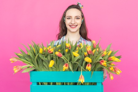 Close-up portrait of brunette young woman with bunch of tulips on pink background