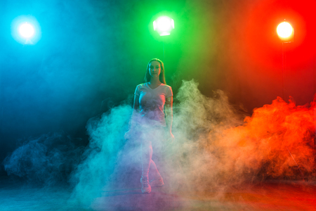 Cheerleading young woman dancing on colourful dark background