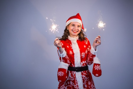 People, christmas and holidays concept - young woman in santa costume with bengals on grey background