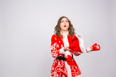 Young woman in red christmas santa claus costume dancing on white background with copy space