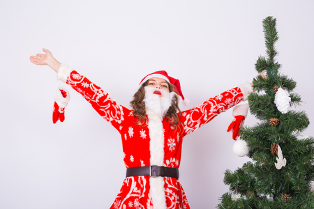 Funny girl in wearing xmas santa costume over christmas tree background. Holidays, joke and people concept