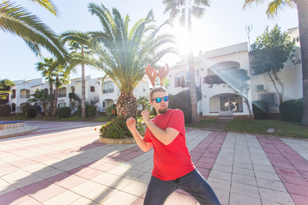 Holidays and people concept - funny man in christmas deer horns dancing outdoors Stock Photo