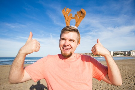 Holidays and Christmas concept - Man wearing rudolph horns with thumbs up at the beach Stock Photo