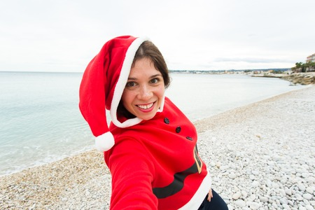 Christmas, humor and people concept - young woman in Santa suit making selfie near the sea at summer