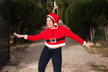 Christmas, holidays, humor and people concept - funny happy woman in santa suit dancing outdoors