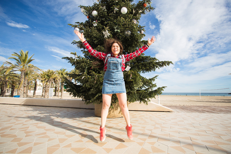 People, holidays and fun concept - happy young woman jumping near Christmas tree