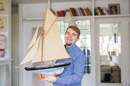 Hobby, interior and collecting concept - handsome man holding the layout of a sailboat in the room Stock Photo