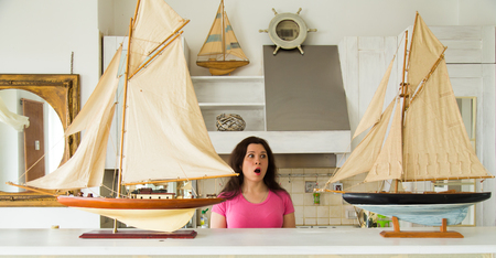 Hobby, emotions and collecting concept - young surprised woman looking to layout of a sailboat in the kitchen