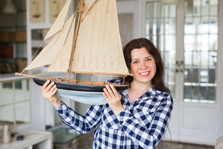 Hobby, interior and collecting concept - young woman holding the layout of a sailboat in the room