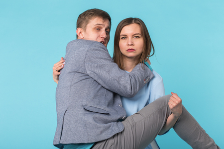 Family problems, responsibility, feminism and relationship concept - Woman carrying man in her arms on blue background
