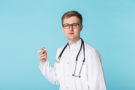 Stressed doctor smoking cigarettes on blue background