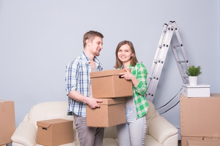 Family, new apartment, emotions and relocation concept - couple of young happy people holding boxes. Moving in a new apartment