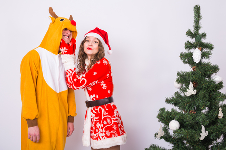Holiday, Christmas and joke concept - Funny man in deer costume and woman in Santa Claus costume are fooling around near Christmas Tree