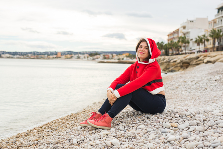 Christmas and holidays concept - dreaming woman in santa costume on sandy beach