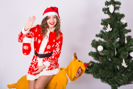 People, christmas and family concept - young woman in christmas costume sitting piggyback on deer