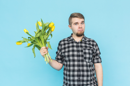 Caucasian handsome man with bunch of yellow tulips on blue background.