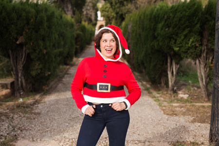 People, emotions and christmas concept - young brunette funny woman in santa suit dancing outdoors