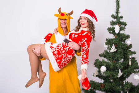 Holiday, Christmas and joke concept - Funny man in a deer costume holding woman in Santa costume on hands over christmas tree background