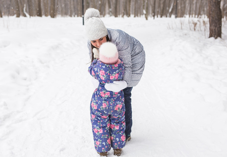 Winter, family and childhood concept - mother is walking with her little daughter in snowy forest and hugging