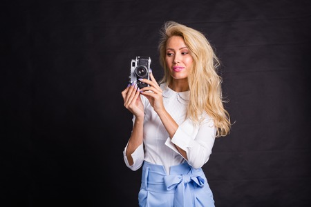 Leisure, fashion and people concept - young blonde woman making a photo and smiling on black background with copy space
