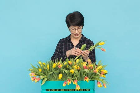 Charming brunette female florist sorts out tulips in the box, selects them for the future flower arrangement