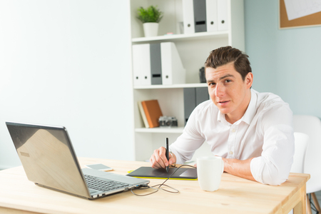 Designer, technologies, people concept - man using graphic tablet in office and looking at you