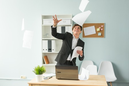 Business, humor and people concept - Handsome and young man in suit throws up sheets of paper in office Archivio Fotografico