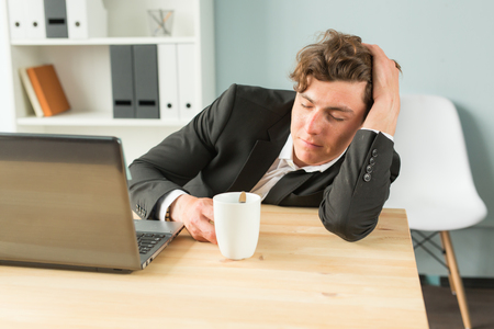 Business, humor and people concept - Handsome man sleeping at workplace