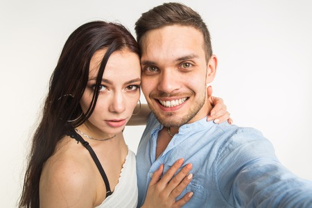Relationship and people concept- man taking selfie with his wonderful woman on mobile phone over white background 版權商用圖片