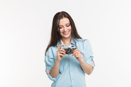 Happy european female model with dark hair enjoying indoor photoshoot. Young woman is looking at her vintage camera on white background Stockfoto
