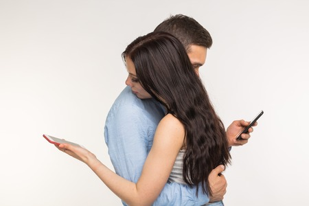 Smartphone addiction concept - Young couple using internet on mobile phone, ignoring each other. They are bored and sad