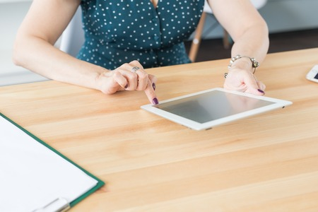 Business, technology and people concept - Close up of female hands holding a tablet on office table