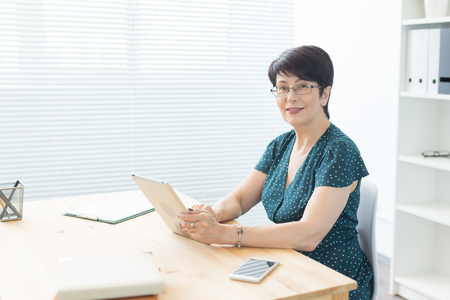 People and technologies concept - Middle aged business woman using a tablet in office Stock Photo