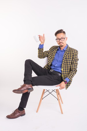 Business and people concept - Handsome man sits in his chair and holding a cup on white background Stock Photo