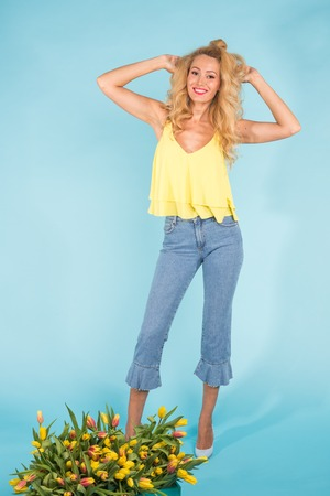 Portrait of a cheerful young blonde woman posing near box of tulips on blue background