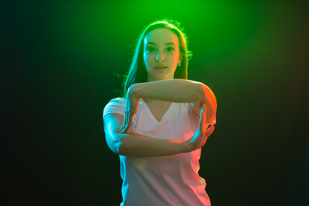 Young athletic female dancing street dance in studio