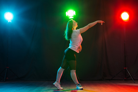 Modern dance, sport and people concept - young woman dancing jazz funk in the darkness under colourful light Banque d'images - 110813619